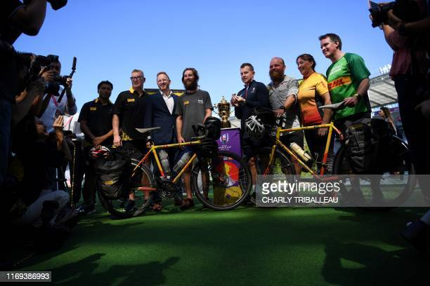 Cyclists Ron Rutland and James Owen pose with referee Nigel Owens at the Tokyo stadium in Tokyo on September 19 after they delivered the whistle that...