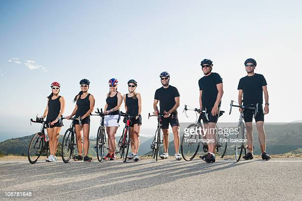 cyclists standing beside their bikes on the side of the road - cycling event stock pictures, royalty-free photos & images