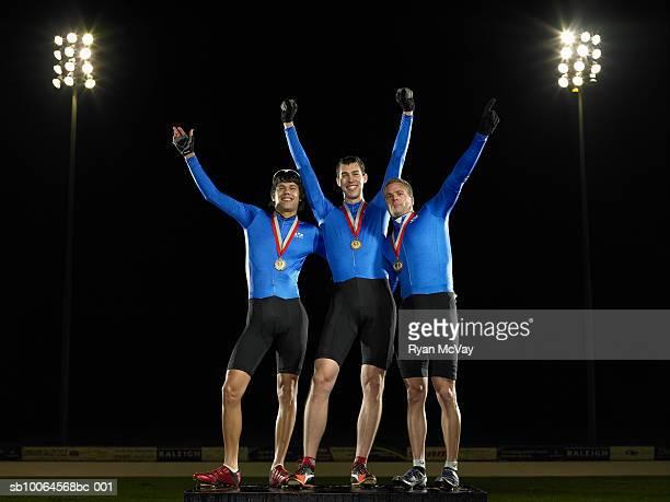 cyclists standing on podium, celebrating first place - podio del vincitore foto e immagini stock