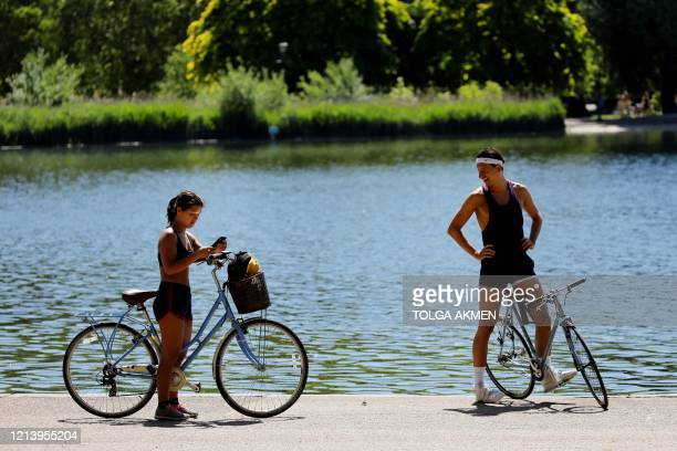 Cyclists stop with their bikes in the afternoon sunshine in Hyde Park, London, on May 19 following the relaxing of lockdown restrictions imposed due...
