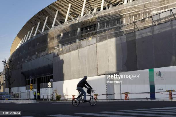 A cyclists travels past the construction site of the New National Stadium the main venue for the Tokyo 2020 Olympic and Paralympic Games in Tokyo...