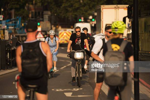 Cyclists uses a bicycle lane beside trucks in London, U.K., on Monday, Aug. 10, 2020. With a budget of £2 billion over the next five years, Britain...