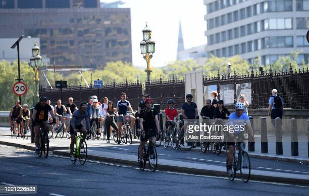 Cyclists wait at traffic lights outside the Houses of Parliament on April 26 2020 in LondonEngland The British government has extended the lockdown...