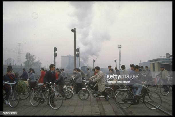 Cyclists waiting at railroad crossing as air polluting coal burning steam train passes through