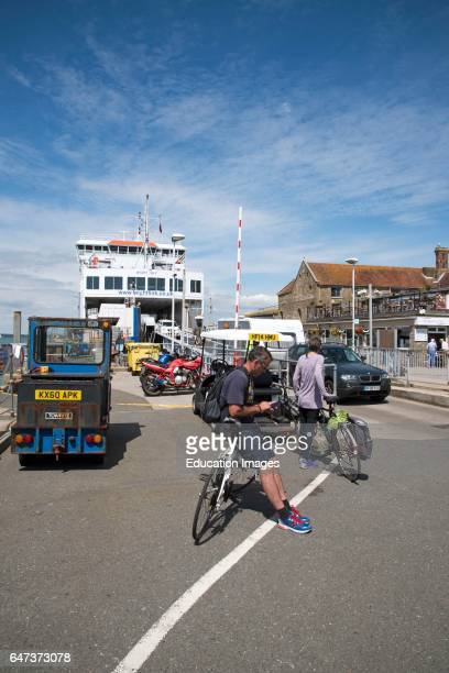 Cyclists waiting to board a roll on roll off ferry berthed on the waterfront.
