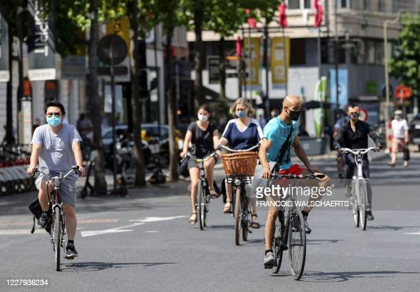 Cyclists wear protective facemasks as they travel on a street in Antwerp on August 6 as authorities impose additional measures to attempt to curb the...