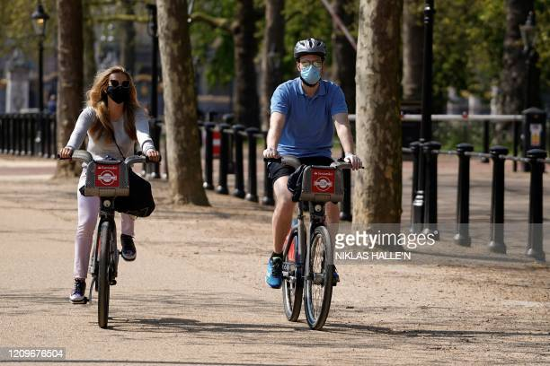 Cyclists, wearing a face mask as a precautionary measure against COVID-19, ride their bicycles on The Mall road, outside Buckingham Palace in central...