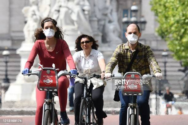 Cyclists wearing face masks ride along The Mall near Buckingham Palace in central London on May 16 following an easing of lockdown rules in England...