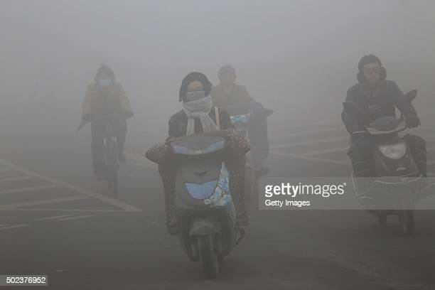 Cyclists wearing masks ride along a road in heavy smog on December 23, 2015 in Zhengzhou, China. According to the Ministry of Environmental...