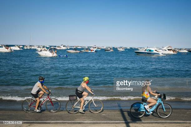 Cyclists wearing protective masks ride past boats anchored on Lake Michigan in Chicago, Illinois, U.S., on Saturday, Sept. 5, 2020. While new...