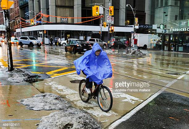 TORONTO ON DECEMBER 21 A cyclists wears a rain poncho at the corner of Bay and Queen Sts Below freezing temperatures brought rain to downtown Toronto...