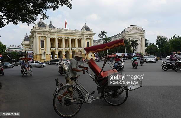 A cyclo driver waits for tourists in front of the the onehundredyearold Opera House which was built during French colonial rule in downtown Hanoi on...