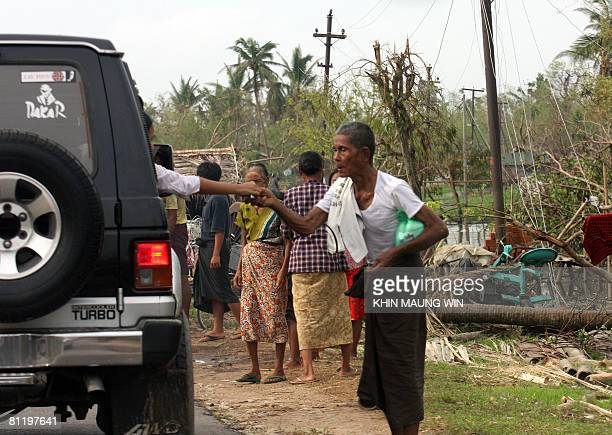 A cyclone affected man receives some money from a local donor in Dedaye some 130 kms south west of Yangon on May 21 2008 Villagers in parts of...