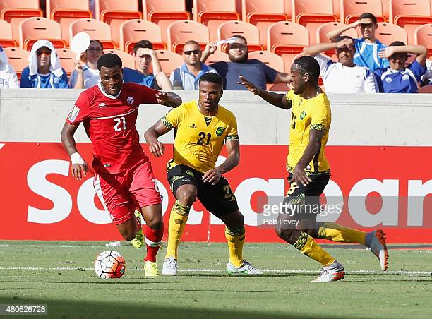 Cyle Larin of Canada avoids pressure from Jermaine Taylor of Jamaica and JeVaughan Watson at BBVA Compass Stadium on July 11 2015 in Houston Texas