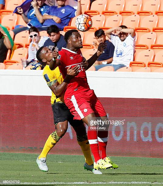 Cyle Larin of Canada heads the ball away frokm Jermaine Taylor of Jamaica in the first half at BBVA Compass Stadium on July 11 2015 in Houston Texas
