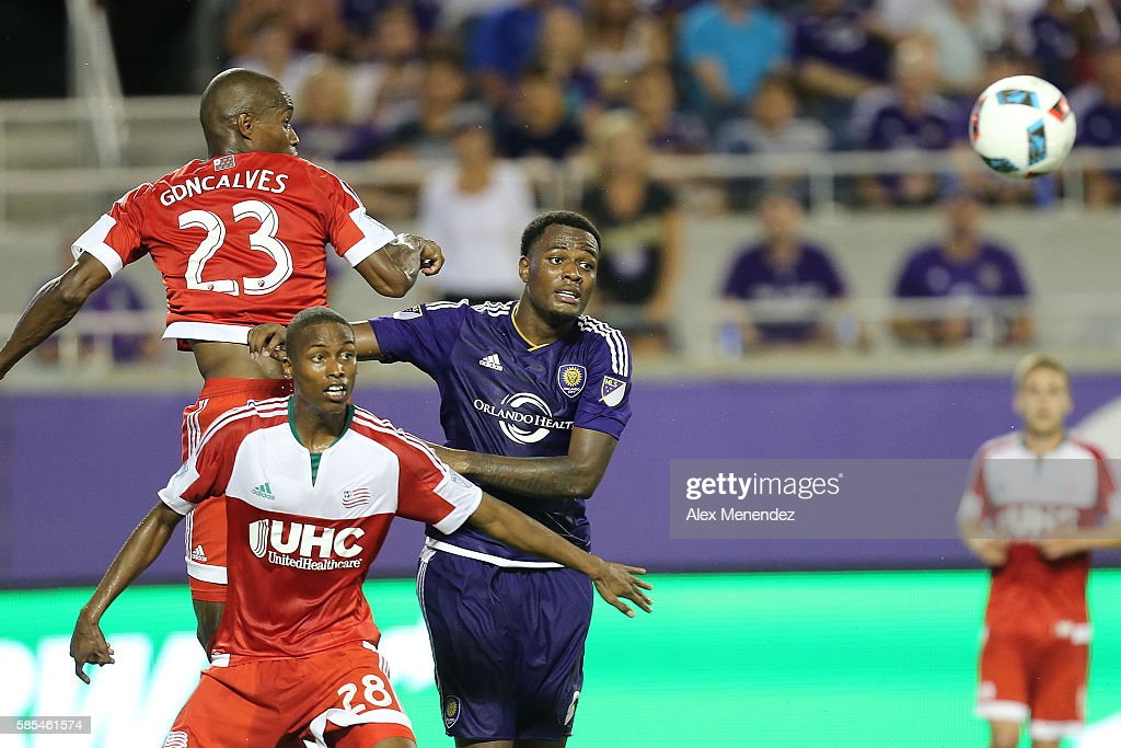 Cyle Larin #9 of Orlando City SC fights against Jose Goncalves #23 and London Woodberry #28 of New England Revolution during a MLS soccer match at Camping World Stadium on July 31, 2016 in Orlando, Florida.