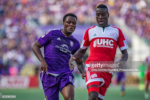 Cyle Larin of the Orlando City Lions races against JeVaughn Watson of the New England Revolution at the Citrus Bowl in Orlando Florida on April 17...