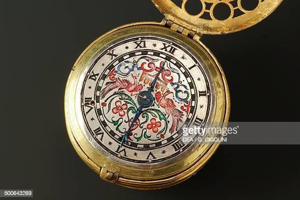 Cylindrical brass clock with silver dial decorated with polychrome enamels the watch has an alarm rocker arm mechanism and pig bristle regulation The...