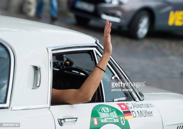 Cyndie Allemann waves out of her Mazda Cosmo 110 S built in 1968 at the start of the HamburgBerlin Vintage Car Rallye in Hamburg Germany 24 August...