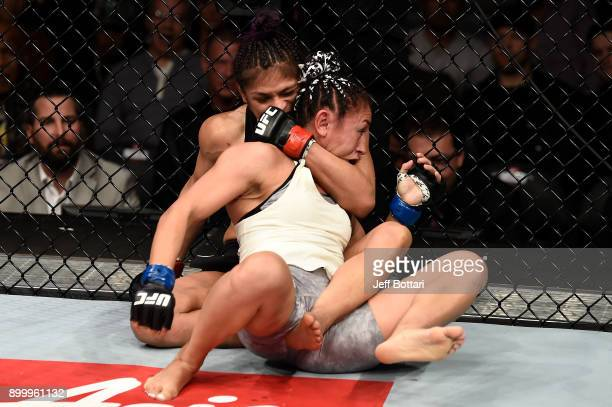 Cynthia Calvillo attempts a rear choke submission against Carla Esparza in their women's strawweight bout during the UFC 219 event inside TMobile...