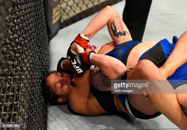 Cynthia Calvillo attempts to submit Joanne Calderwood of Scotland in their women's strawweight bout during the UFC Fight Night event at the SSE Hydro...
