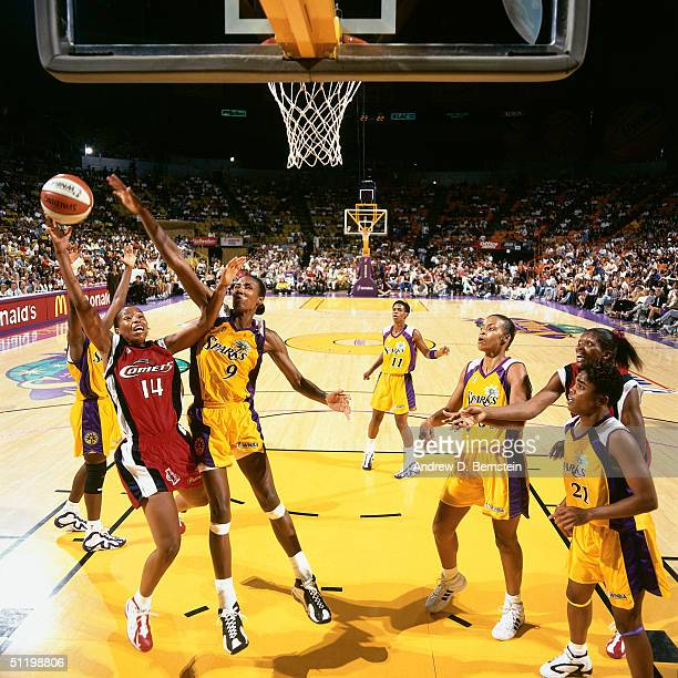 Cynthia Cooper of the Houston Comets drives to the basket against Lisa Leslie of the Los Angeles Sparks during a WNBA game at the Staples Center in...