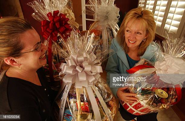 ROCK CO DECEMBER 17 2003 Cynthia <cq> McKay president and CEO of Le Gourmet gift basket Inc right is wrapping gifts for her employees with help from...