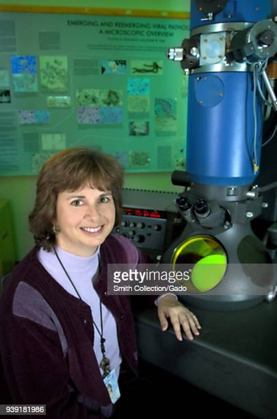 Cynthia Goldsmith a Centers for Disease Control research biologist sitting in front of a transmission electron microscope 2004 Image courtesy Centers...