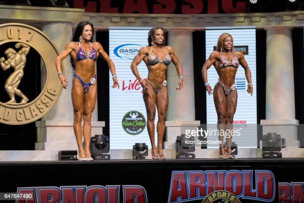 Cynthia Netto Donya Jackson and Michelle Bailey stand on stage as they are judged for Amateur Figure Overall Champion at the Arnold Amateur IFBB /...