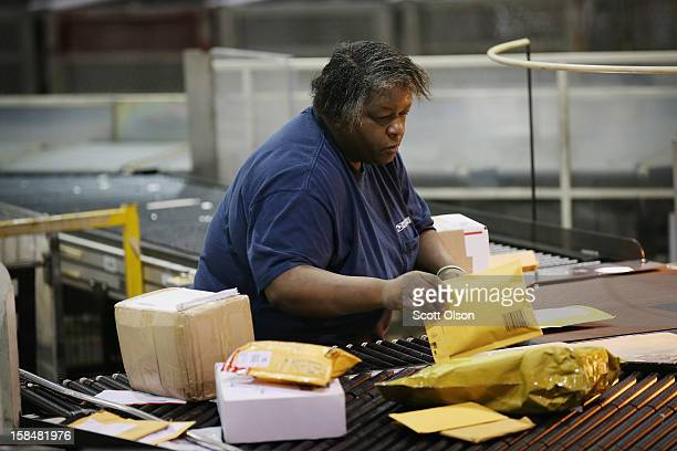 Cynthia Peterson sorts mail at the United States Postal Service Chicago Logistics and Distribution Center on December 17 2012 in Elk Grove Village...