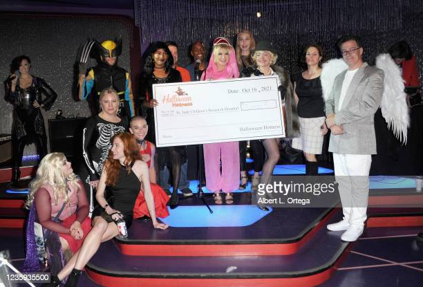 """Cynthia Rothrock, Jessica 'Sugar' Kiper, Brian Sikoff and the cast of """"Resident Evil: Village"""" pose with the ceremonial check to St. Jude for Six..."""