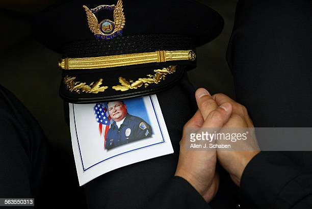Cypress Police Captain Mark Yokoyama folds his hands next to a program for Buena Park police corporal Tyler M. Pinchot during a memorial service at...