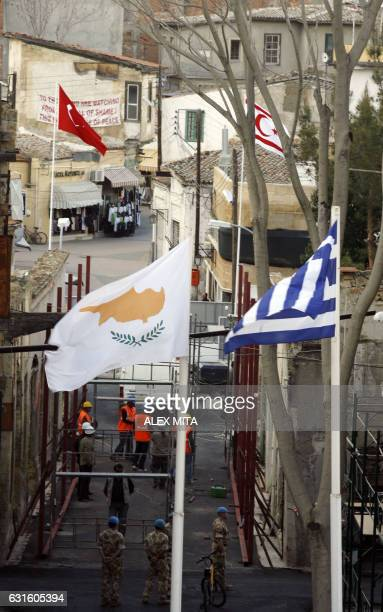 Cypriot and Greek flags fly across the UNcontrolled buffer zone from Turkish and Turkish Republic of Northern Cyprus flags as UN soldiers and...