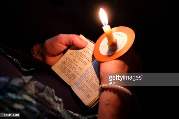 A Cypriot Greek Orthodox worshipper holds a candle and prayer book outside Faneromeni church in the old city of Nicosia during the Easter Saturday...