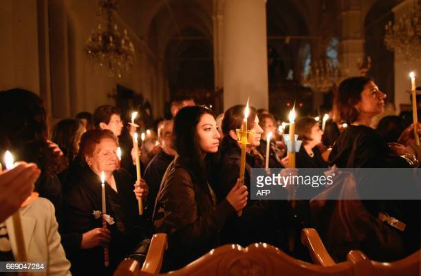 Cypriot Greek Orthodox worshippers queue up to exit Faneromeni church in the old city of Nicosia carrying candles in preparation for the Easter...