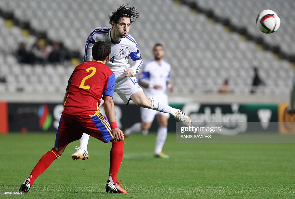 Cypriot player Giorgos Merkis (back) heads the ball in front of Andorra's Cristian Martinez during their Euro 2016 Group B qualifying match at the GSP Stadium in the capital Nicosia on November 16, 2014.