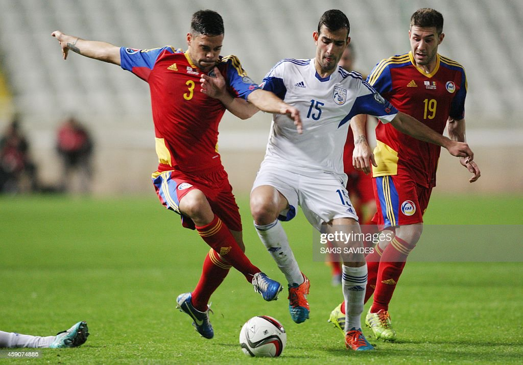 Cypriot player Marios Antoniades (C) fights for the ball with Andorra's Marc Vales (L) and Ivan Lorenzo during their Euro 2016 Group B qualifying match at the GSP Stadium in the capital Nicosia on November 16, 2014.