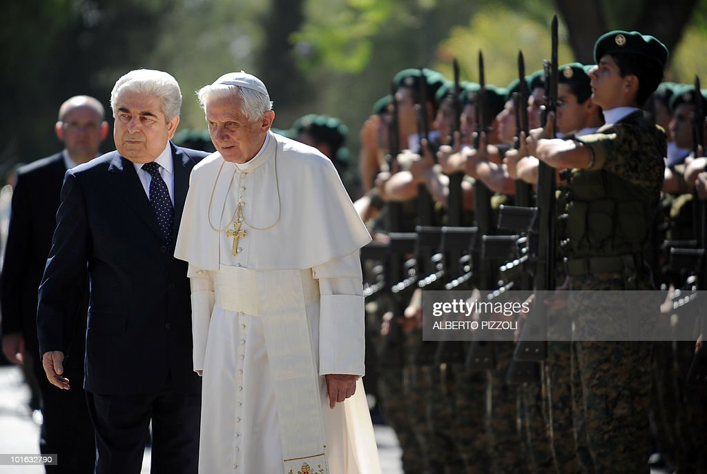 Cypriot President Demetris Christofias (L) escorts Pope Benedict XVI as he reviews the honour guard upon arrival at the presidential palace in Nicosia on June 5, 2010 on the second day of the pontiff's visit to the mainly Greek Orthodox Mediterranean island of Cyprus.