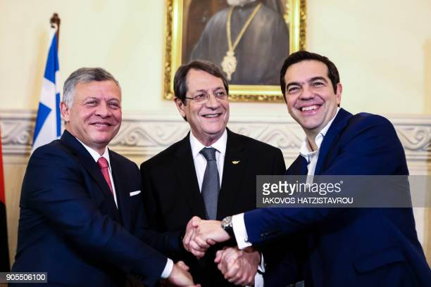 Cypriot President Nicos Anastasiades Greek Prime Minister Alexis Tsipras and Jordanian King Abdullah II shake hands during a trilateral meeting in...