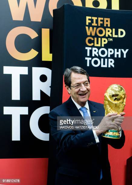 Cypriot President Nicos Anastasiades holds the FIFA World Cup Trophy during an official ceremony upon its arrival at the old airport of the coastal...