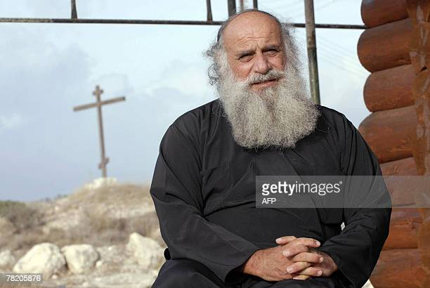 Cypriot priest Savvas Michaelides sits on the steps of his humble church near the coastal town of Limassol 15 November 2007 Standing outside his...