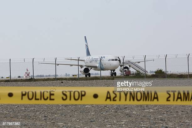 Cypriot security forces cordon off the area around Larnaca airport where an EgyptAir Airbus A320 is seen on the tarmac after being hijacked and...
