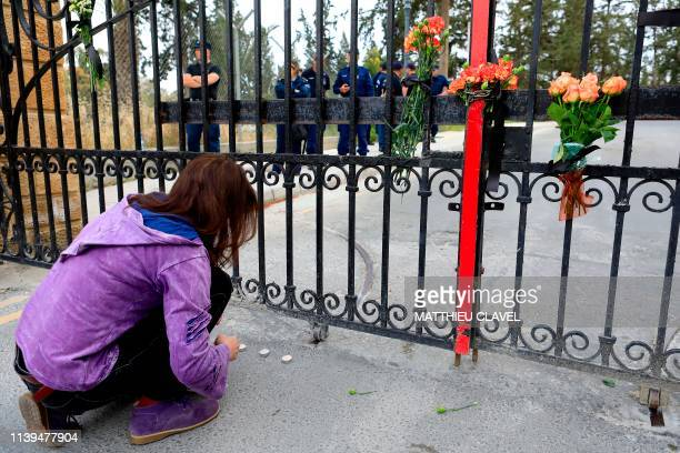 A Cypriot woman lights a candle as protesters demonstrate in support of the victims of a suspected serial killer in front of the presidential palace...