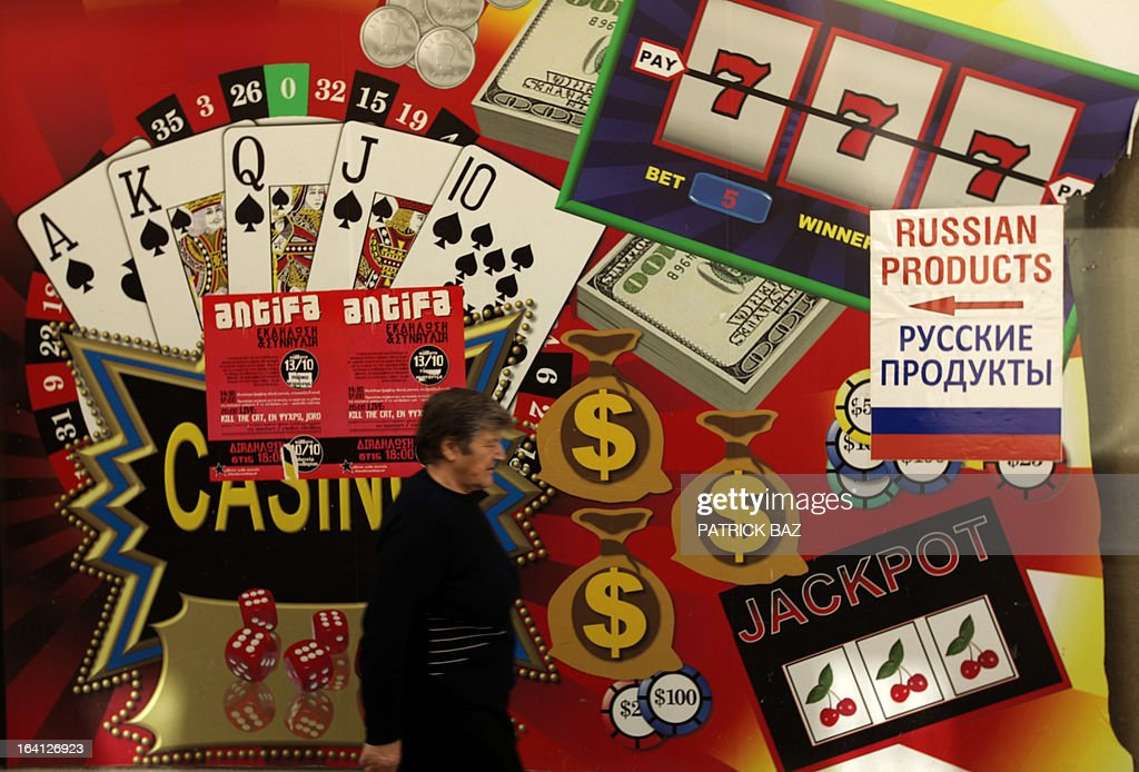 A Cypriot woman walks past a sign advertising a shop selling Russian products, plastered on a closed betting shop in Nicosia's Ledra street on March 20, 2013