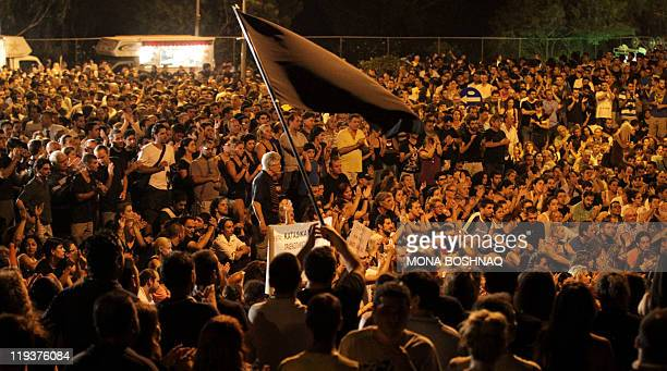 A Cypriot youth waves a black flag in a sign of mourning as hundreds protest outside the presidential palace in Nicosia on July 19 2011 demanding the...