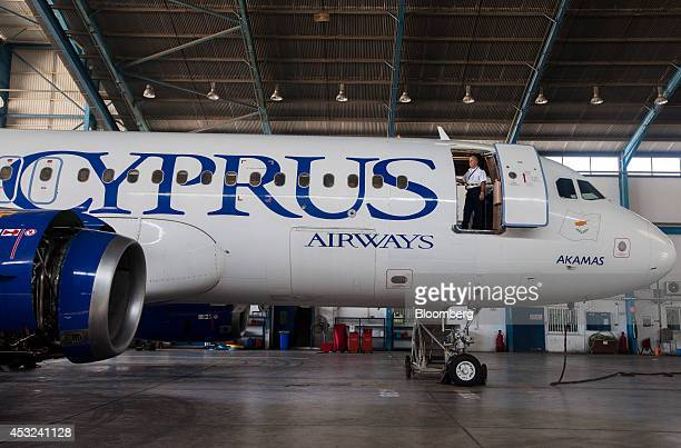 A Cyprus Airways Public Ltd engineer looks out from the doorway of an Airbus A320 aircraft manufactured by Airbus Group NV during routine servicing...