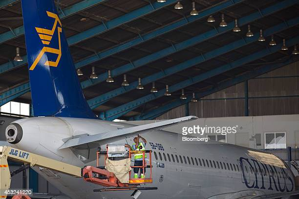 A Cyprus Airways Public Ltd engineer stands on a JLG Industries Inc lift to service the elevator of an Airbus A320 aircraft manufactured by Airbus...