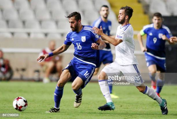 Cyprus' Charis Kyriakou vies for the ball against Bosnia and Herzegovina's Miralem Pjanic during their World Cup 2018 Europe qualifying match between...