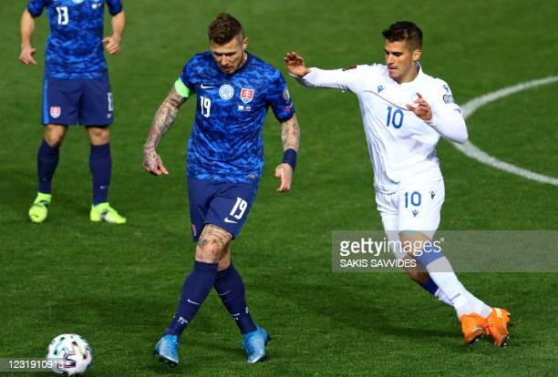 Cyprus' forward Pieros Sotiriou marks Slovakia's midfielder Juraj Kucka during the 2022 FIFA World Cup qualifier group H football match between...