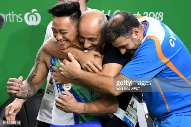 Cyprus' Marios Georgiou is hugged after winning the men's floor exercise final artistic gymnastics event during the 2018 Gold Coast Commonwealth...